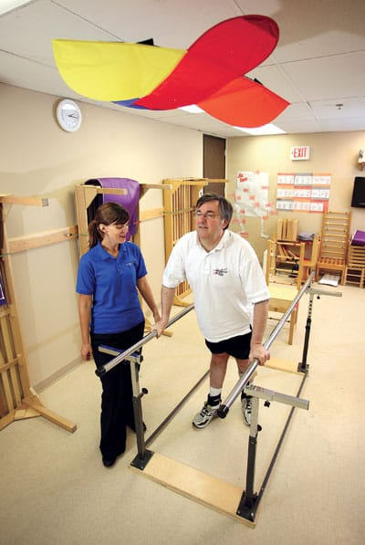 A big step: Keith Sherwood, who has MS, does his walking exercises with the help of Beth Brydon from the March of Dimes Conductive Education program. Brydon says one of the biggest benefits that people get from the program is improved confidence.