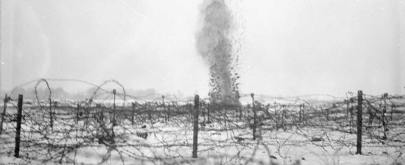 A shell bursting amongst the barbed wire entanglements on the battlefield near Beaumont-Hamel, France, taken several months after the Newfoundland Regiment's tragedy, in December 1916.