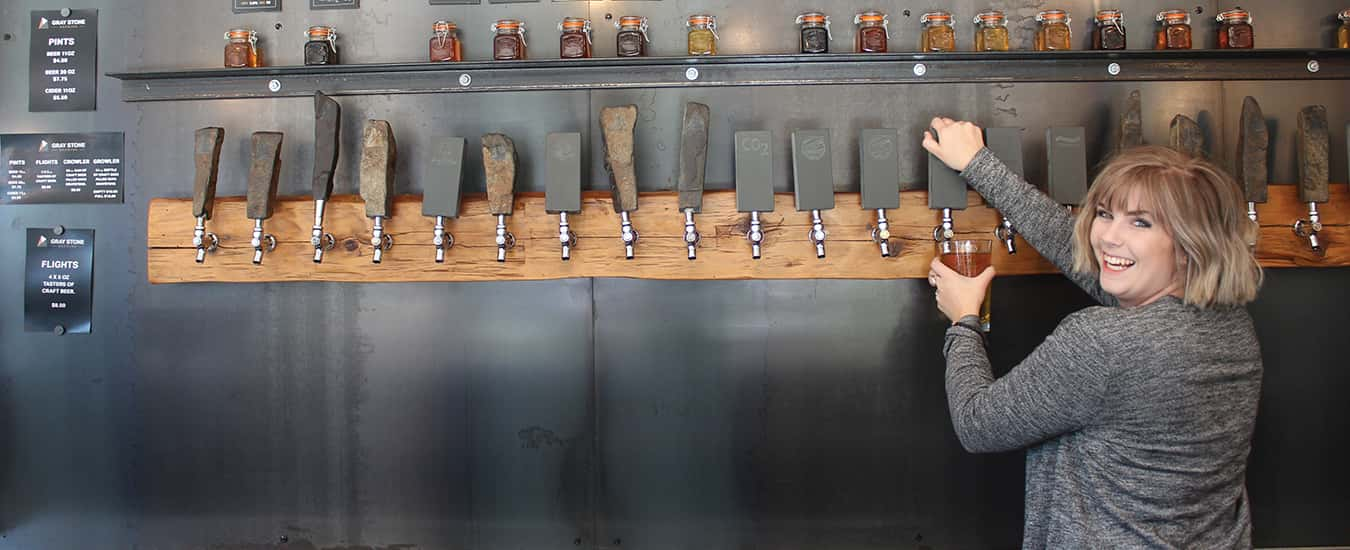 Libby Boudreau pulls on stone-handled beer taps at Graystone Brewing in Fredericton, NB.