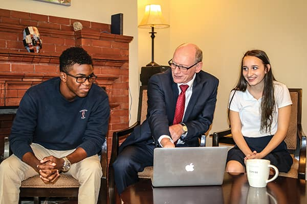 Landmark's headmaster, Peter Coll (centre) jokes with a couple of students.