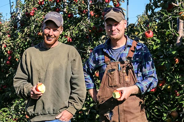 Brothers Jake and Travis Pearson enjoy the fruits of their labours in their orchard.