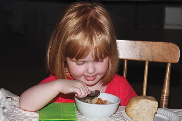 Four-year-old Nadia Gallant has her first taste of fricot at the Albert County Museum, Hopewell NB.